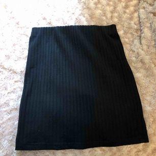 En ribbad svart tajt kjol, likadan som den vita.