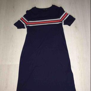 En marinblå klänning från Bershka med röda och vita detaljer. Perfekt strandklänning eller finklänning som inte är använd många gånger. Kontakta vid intresse💞💞 Nypris: 300:-