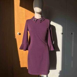 En lila klänning med elegant krage i storlek 38. Trekvartsärmar som slutar i volang. Blixtlås på baksidan av klänningen. Aldrig använd, prislappen sitter kvar.