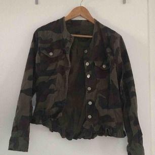 Jacka med kamouflage-mönster med en mindre peplum/volang längst ner. Storlek 38 men passar även 36. Använd 1 gång så väldigt bra skick!