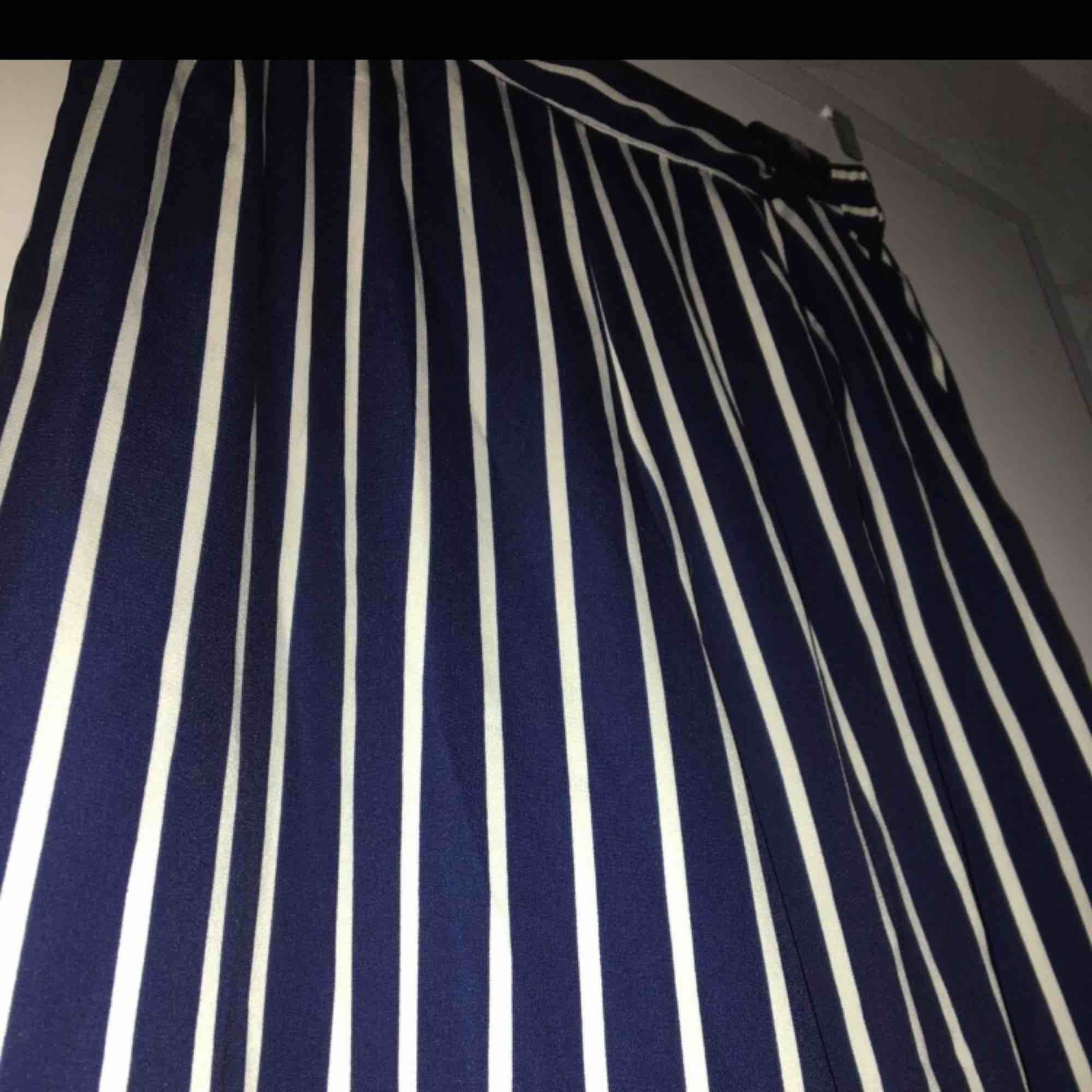 Mörkblå byxor med flow samt vita ränder. Använda 1-2 gånger. Storlek M.. Jeans & Byxor.