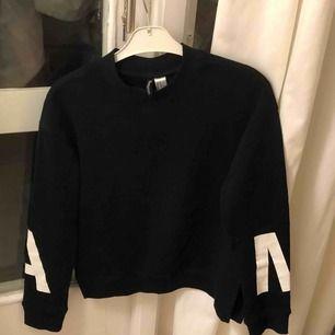 Svart sweatshirt aldrig använd med slitsar på sidan(små) På ärmarna står d a och m på var sin sida