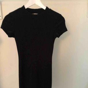 Tajt svart klänning som framhäver formerna