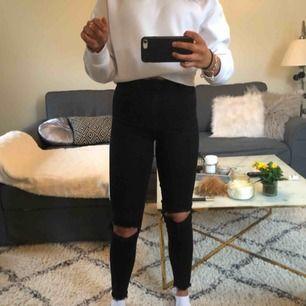 Svart jeans med hål på knäna
