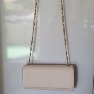 Benvit handväska med guldkedja. Lite smutsig på ovansidan (se bild 2). Ett stort fack samt ett litet innefack. Frakt tillkommer.