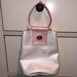"""Äkta vintage väska från Christian Dior i vit och ljusrosa material med guldiga detaljer! Står """"Parfums Christian Dior"""" i guld. Super söt och köpt second hand för ca 1500kr!! Passa på🥰🍒"""