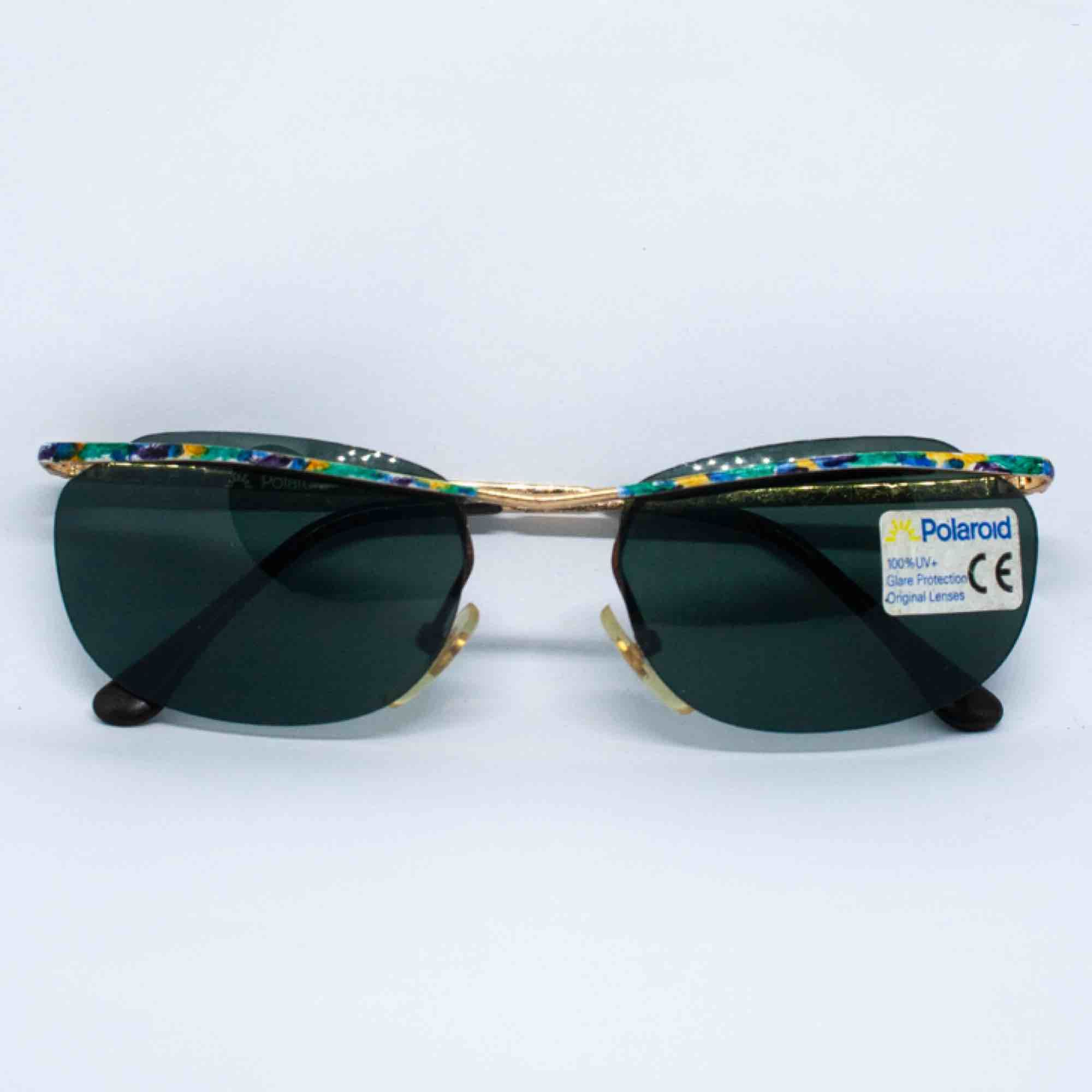 Vintage Y2K 90s 00s Polaroid cyber slim sunglasses in dark green and colorful frame 100% UV+ Barely visible sign of wear, if any Measurements: Frame: 13.5 cm width: 3.8 cm temple: 13 cm Free shipping. Accessoarer.