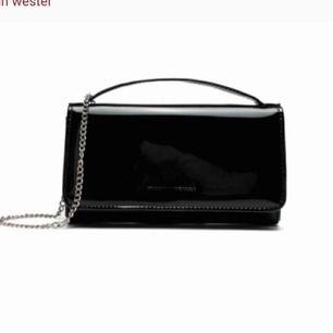 En svart lackad väska från Carin Wester,verkligen supersnygg!🤩🤩 Den har prislapp kvar och är inte använd. Matchar till allt och kan piffa upp en vanlig outfit