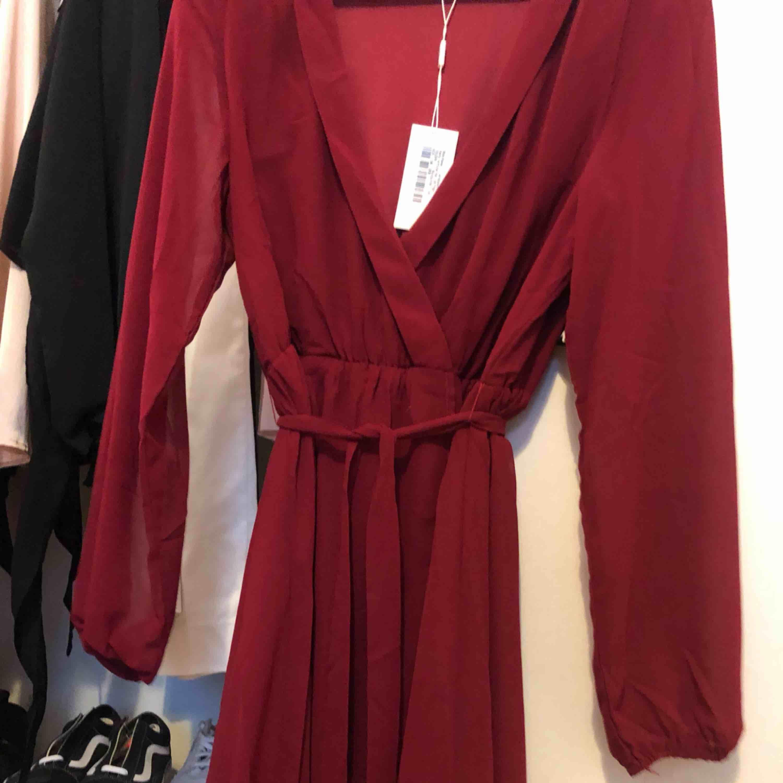 Vinröd klänning med knytning . Klänningar.