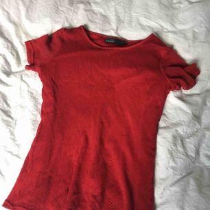 Röd net tisha som glittrar då den har tröja med glitter som är sytt under nätet.