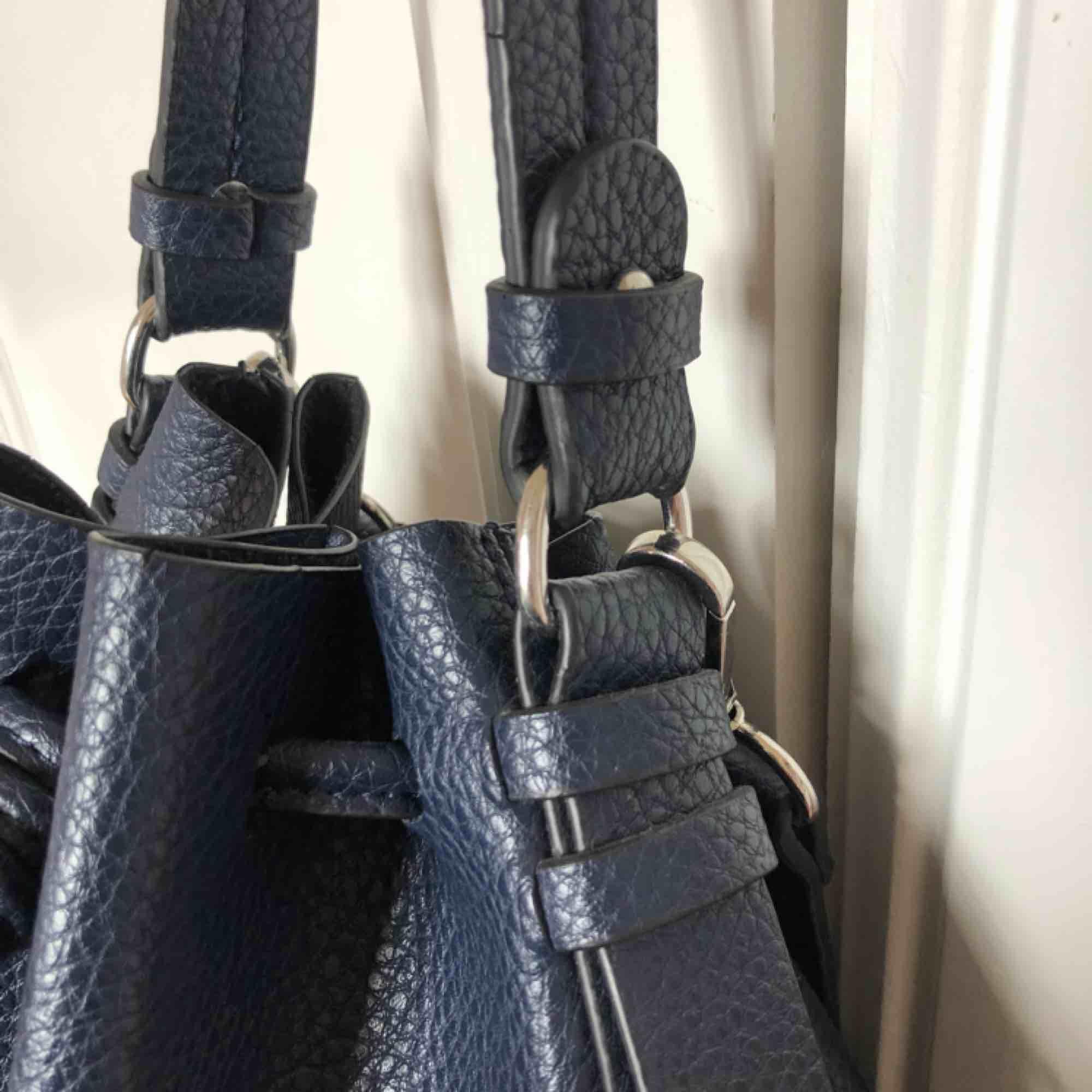Super snygg, mörkblå väska i skinnimitation. Väskan är i superfint skick, endast använd 2 ggr. Finns två inner fack!. Väskor.