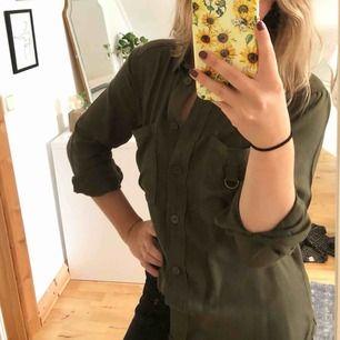 Militärgrön skjorta med små detaljer på bröstfickorna. Köparen står för frakten! 🛍
