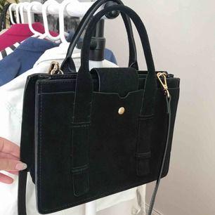 Väldigt fin svart väska från mango i äkta suede med gulddetaljer. Inte mkt använd alls. Justerbar axelrem