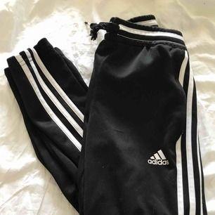 Svarta Adidas byxor med 3 vita streck på varje sida. Jätte fina men ena snöret är lite trasigt (sista bilden). Strl XS / 152, 50kr🌹
