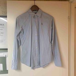 Ljusblå långärmad skjorta från Ralph Lauren i slim fit modell. Använd ett fåtal gånger. Mycket fint skick.