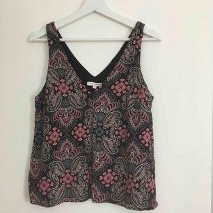 Mönstrat linne från KappAhl i svart, vitt, rosa och rött. Djup v-ringning både i fram och i bak. Storleken angivet på plagget är 38 men det är mer som 40/42. Köparen betalar frakten.