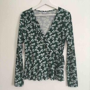 Blommig blus i vitt och mörkgrönt från Gina. Blankt och följsamt tyg. Omlott med knyte (men plagget är sytt, så knytet är bara för syns skull). ✨