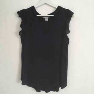 Mörkblått linne storlek S men passar även M. Framsida av tunt blus tyg, baksida av stretchigt t-shirt material, volang ärmar✨ Köpare betalar frakten.