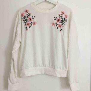 Vit sweatshirt med blomrankor vid axlarna. ✨ Köparen betalar frakten
