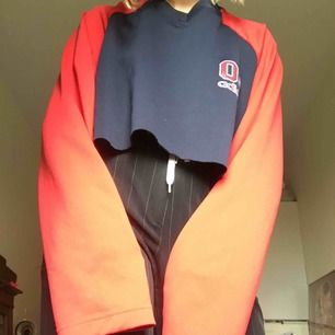 Oversize vintage Adidaströja. Mörkblå med röda ärmar. Passar storlek S-XL. Avklippt modell.