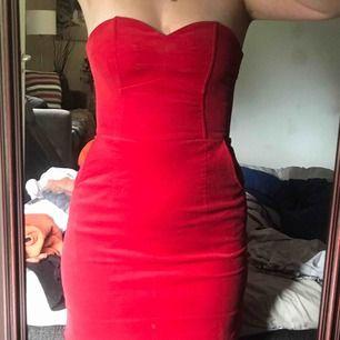 Röd axelbandslös klänning med fickor på sidan. Väldigt stretchigt material