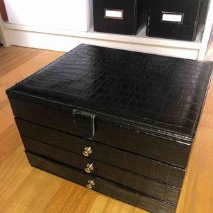 Stor smyckeskrin med svart ormskinn (fejk). Massor av fack och lådor. Pris kan diskuteras! Möts gärna i Stockholm.