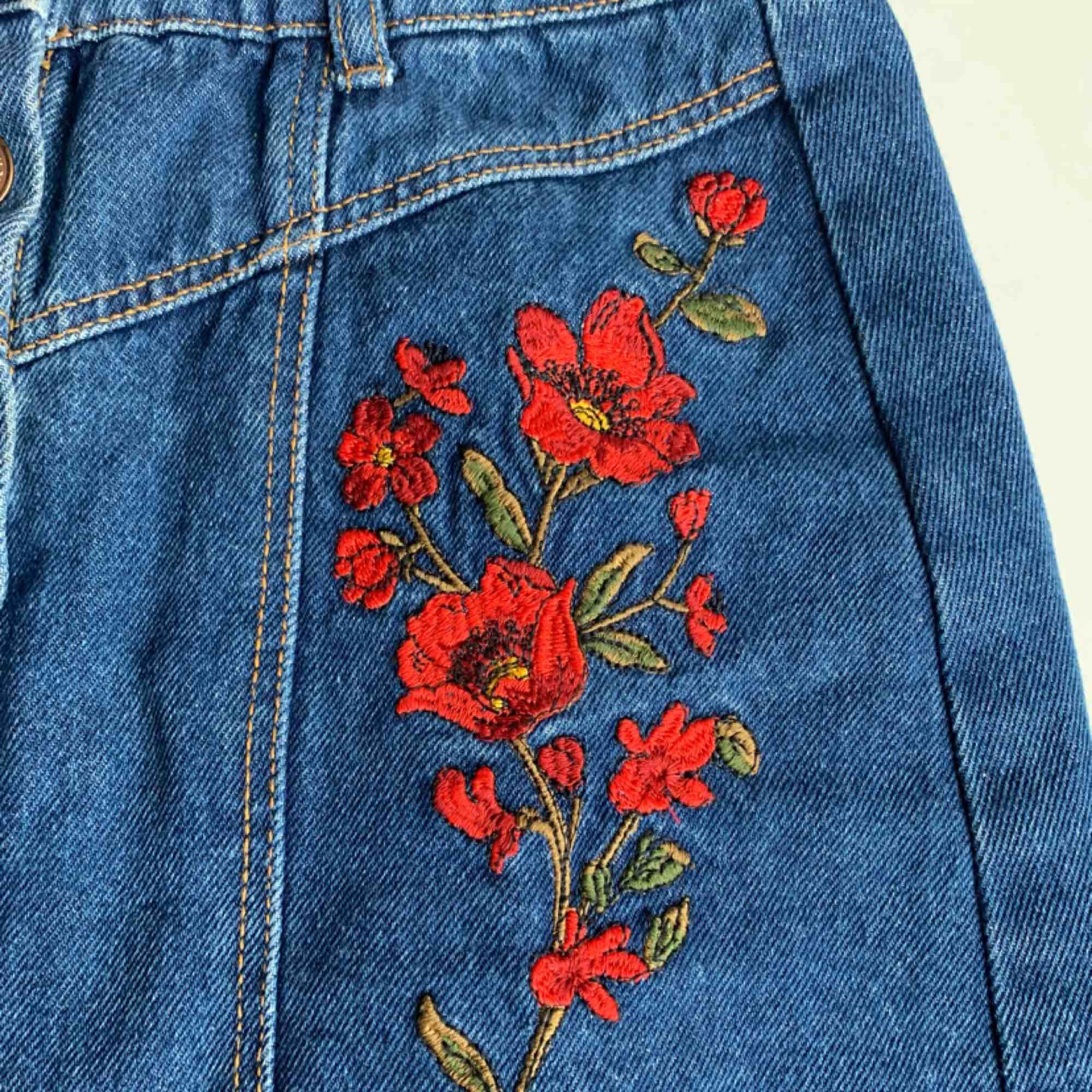 supersöt jeanskjol från stradivarius. använd fåtal gånger. fina broderade vallmoblommor på både höger o vänstersida om knapparna🧡 köparen står för frakten.. Kjolar.