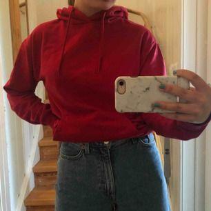 Röd hoodie med snören och luva, köparen står för fraktkostnad