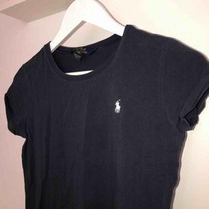 En assnygg väldigt mörkt blå Ralph Lauren t-shirt jag fått i julklapp. Storlek XL i barnstorlek vilket motsvarar XS/S. Bra passform, formar sig efter kroppen. Köpt för ca 500 kr. Precis som ny.