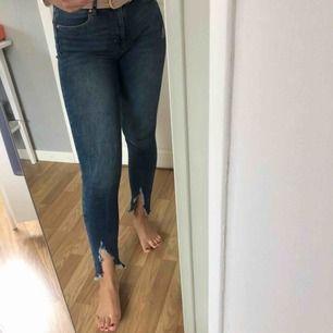 Asballa jeans med slitningar nedtill