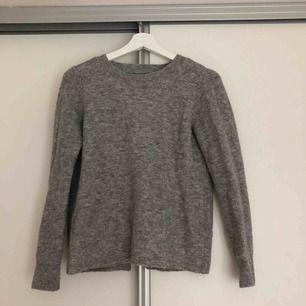 En grå långärmad tröja från Abercrombie & Fitch med en öppning i ryggen.  Storlek: XS. Köparen står för frakt.