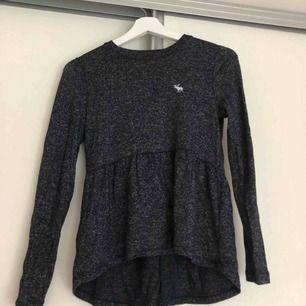 En långärmad blå/grå tröja från Abercrombie & Fitch från barnavdelningen i storlek 11/12.