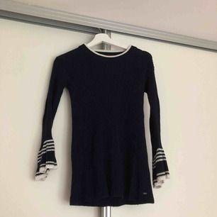 En långärmad tröja från Tommy Hilfiger. Marinblå med vita detaljer. Tröjans ärmar är vida i slutet. Storlek: XXS