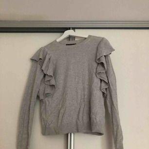 En grå långärmad tröja med volang detaljer. Från: Abercrombie & Fitch  Storlek: XS
