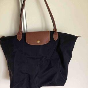 En äkta marinblå Longchamp väska. Köpt i en Longchamp butik i London.  Pris: 500kr. Köparen står för frakten.
