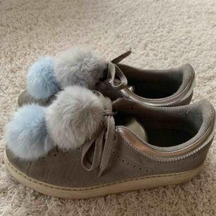 Gråa sneakers med blåa fluffbollar i strl 38. Går även att ta bort bollarna. Kan ni inte mötas upp står ni för frakt. Nästan oanvända.