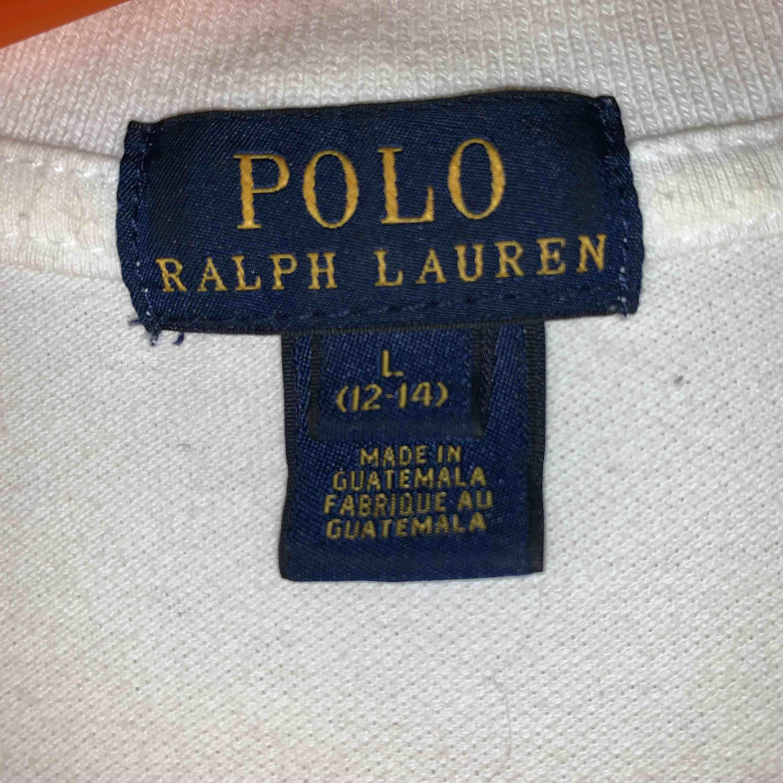 Vit piké med rosa detalj från Ralph Lauren, väl använd men bra skick. Köpt på NK i Stockholm, är en L i barnstorlek men passar som XS. T-shirts.