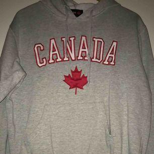 Ljusgrå Hoodie med texten Canada fram, använd men i fint skick. Strl M men passar S också beroende på hur man vill att den ska sitta