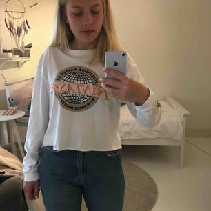 Croppad långärmad t-shirt från Pull&Bear med tryck på bröstet och på armen. Asmysigt och svalt material! Förekommer en fläck som går bort i tvätten. Köparen står för frakten💜