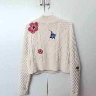 Säljer denna fina stickade tröja med hög krage från Tommy Hilfiger. Detaljer med broderade blommor i olika färger finns på framsidan samt ärmar. Använd ca tre gånger.