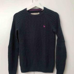 Marinblå, kabelstickad tröja med rosa märke från Jack Wills. Storlek UK 8 vilket motsvarar 36 i EU.