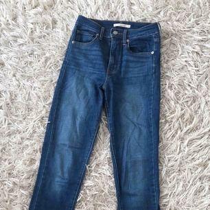 Mörkblå, tajta jeans från Levi's i deras Mile High Super Skinny modell. Väldigt bekväma. Storlek 25 i midja och 32 i längd.