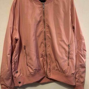En rosa bomberjacka från joy men är märker loul. Den är storlek L men passar någon med M om man vill ha den mer oversized den är tunn men fin!