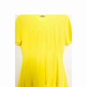 Oanvänd Acne Studios top i citrongul färg med detaljer som framhäver midja.