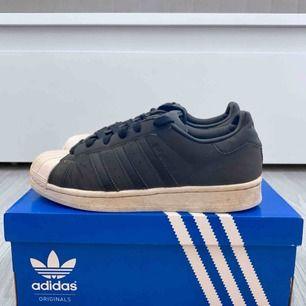 Svarta/gråa Adidas Superstar storlek 37 1/3, använt men bra skick. Obs lådan ingår ej.  Frakt kostar 63kr extra, postar med videobevis/bildbevis. Jag garanterar en snabb pålitlig affär!✨ ✖️Fraktar endast✖️