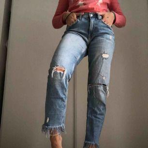 Ett par snygga boyfriend jeans med hål på knäna och fransar längsta ner. Bra passform och snygg ljusblå jeansfärg. Jag är ca 160 cm lång.  Köparen betalar frakten  Och betalar med swish