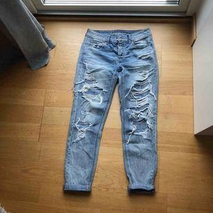 Ljusblå Boyfriend jeans med mycket hål. Lose fit och uppvikta byxben.  köparen betalar frakten, betalas med swish