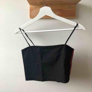 Cropat linne från Urban Outfitter använt fåtal gånger och i väldigt bra skick med dragkedja i bak och två röda ränder på vardera sida.
