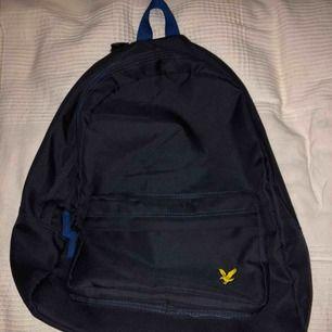 En mörkblå Lyle&Scott ryggsäck. Är i väldigt bra kondition med nästan inga skador, den är bra som ny! Ett litet Lyle&Scott märke vid ytterfaket. Ryms väldigt mycket i den.