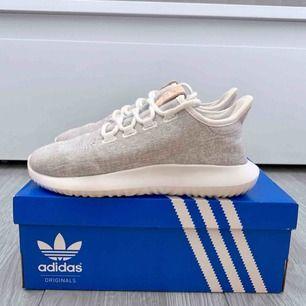 """Vita/gråa Adidas Tubulars storlek 36 2/3 i nyskick, enbart använda en gång. Färgen heter """"shadow"""" Lådan ingår.  Frakt kostar 63kr extra, postar med videobevis/bildbevis. Jag garanterar en snabb pålitlig affär!✨ ✖️Fraktar endast✖️"""
